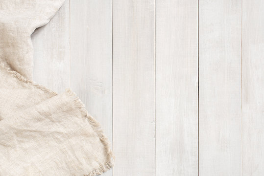 White wooden background decorated with linen napkin