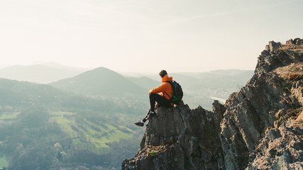 Young man with backpack sitting on rock looking into the landscape. Listening to the silence. Beautiful moment the miracle of nature. Wall mural