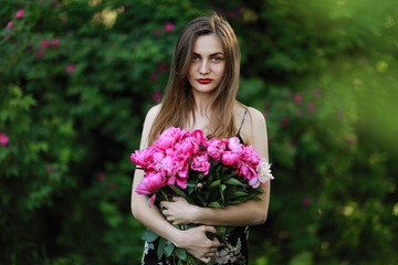 girl in the field of flowers. portrait of a girl with pink flowers