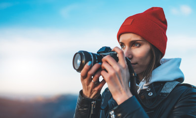hipster tourist girl hold in hands take photography click on modern photo camera, photographer look on camera technology, journey landscape vacation concept, sun flare mountain Fotobehang