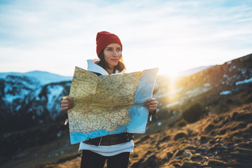 Wall Mural - young girl look and hold in hands map, people planning trip, hipster tourist on background sun flare nature, enjoy journey landscape vacation trip, lifestyle holiday concept, sun mountain