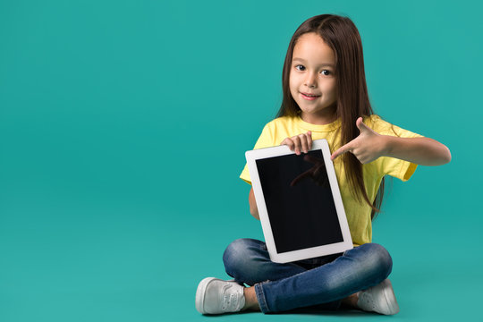 cute little child girl holding blank tablet computer on blue background