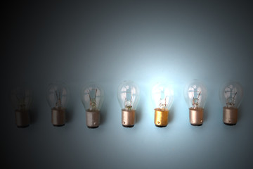 Row of switched off light bulbs with one switched on. Concept of having idea and creativity