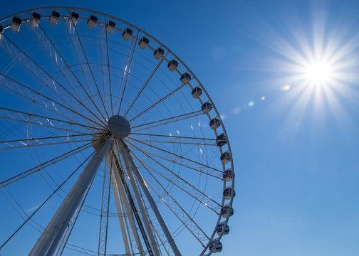Bright sun shines over recreational ferris wheel