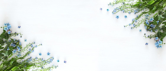 spring bouquet of blue and delicate blue flowers over white wooden background. top view, flat lay