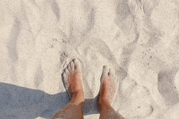 POV of a man standing barefoot on the beach, touching the warm sand. Room for copyspace on the top. Clean natural colors.