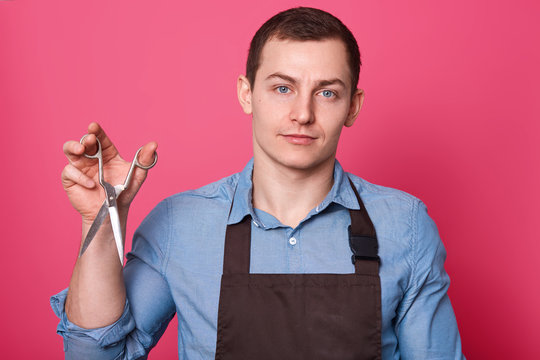 Imagine of barber wears brown apron and blue shirt in one tone with scissors in his hand, ready to do hairstyle for men, poses in babershop against pink background. Grooming concep. Copy space.
