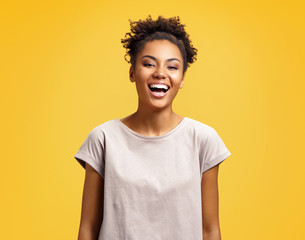 Joyful student laughs at good joke. Photo of african american girl wears casual outfit on yellow background. Emotions and pleasant feelings concept.