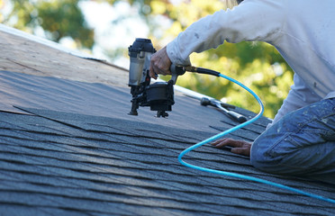 handyman using nail gun to install shingle to repair roof