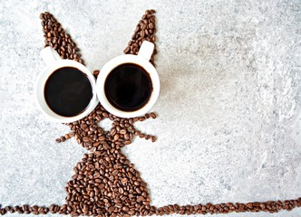 Printed kitchen splashbacks Cafe With fresh coffee beans and two cups of freshly brewed black coffee, a hare is shaped on a bright marble surface - concept with coffee beans as a gift for Easter - with room for text or other elements