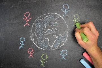 On a dark stone surface, a globe was painted with chalk and different-colored male figures drawn on the outside - concept of diversity and tolerance represented worldwide by a chalk drawing