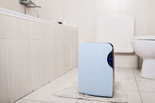 Dehumidifier with touch panel, humidity indicator, uv lamp, air ionizer, water container works in bathroom. Air dryer