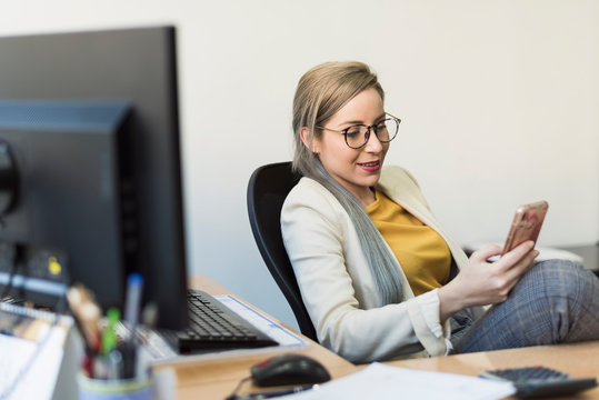 Young woman looking smartphone at work in a break