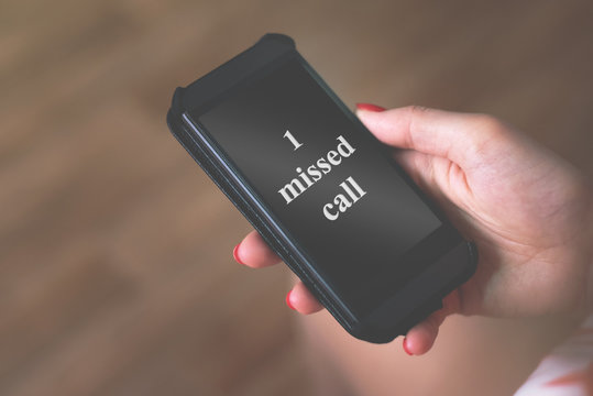 One missed call the inscription on a mobile phone screen in a female hand.