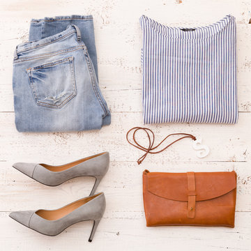 Closeup of fashionable women's accessories: shirt, jeans, shoes, leather clutch and other accessories on a white wooden table