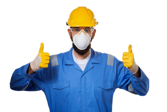 Builder in hard hat in mask and transparent safety glasses raising his thumbs up in working gloves, concept of success and approval, ok gesture, isolated over white background
