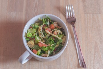 White bowl of colorful salad on table top with steel fork