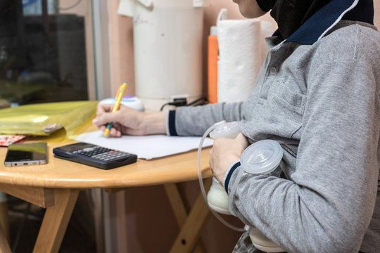 Busy mother pumping breastmilk with automatic breast pump machine while working and writing.