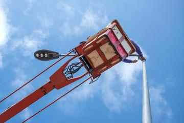 Technician on bucket truck high up of a crane to fix street light.