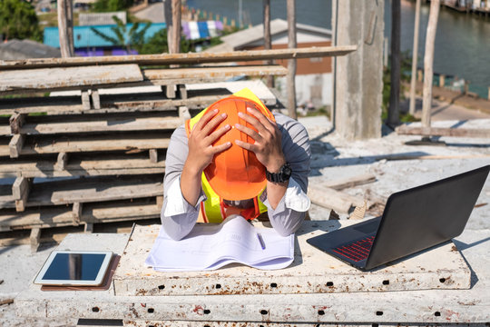 Stress engineer or architect with laptop and tablet holding hands at his head. He is having problems in work. Engineering concept.