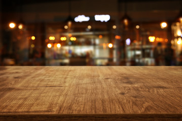 Image of wooden table in front of abstract blurred restaurant lights background Fotomurales
