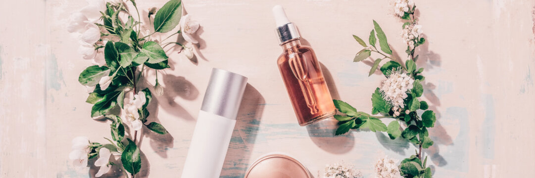 Natural organic cosmetics: serum, cream, mask on wooden background with flowers. Spa concept
