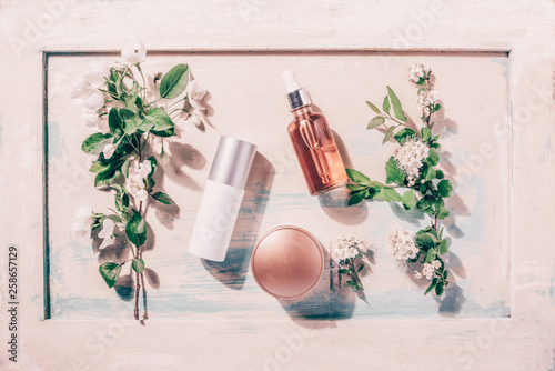 Natural organic cosmetics: serum, cream, mask on wooden background with flowers. Skincare concept