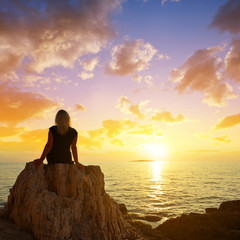 A woman sitting on a cliff is watching the sunset over the sea.