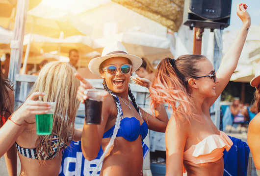 Young woman enjoying at summer beach party. Young female friends dancing an enjoying at beach party
