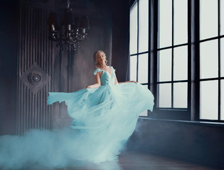 Fotorolgordijn Bestsellers Kids The magical transformation of Cinderella into a beautiful princess in a luxurious dress. Young women are blonde, spinning and dancing in a dark, gloomy room, the dress fluttering on the fly. Art photo