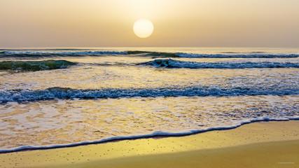 Romantischer goldener Sonnenaufgang über dem Meer am Strand bei leichten Wellen