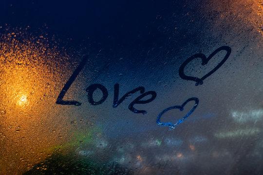 inscription Love on misted glass, night lights bokeh on background