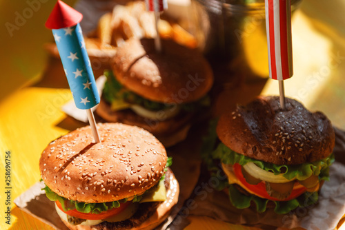 three fresh and juicy burgers with American flag-style fireworks inserted into them. bbq concept picnic to celebrate independence day