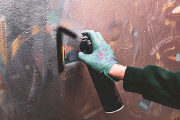 artist hand drawing graffiti  with the aerosole spray paint on the wall can