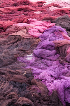 Pile of brown, violet and pink fishing nets