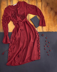 Beautiful unusual outfit presentation for fashion blog, advertising, clothing catalog. Unusual dress burgundy, dark red, cherry, the color of Marsala. Background of parquet boards and black paper.