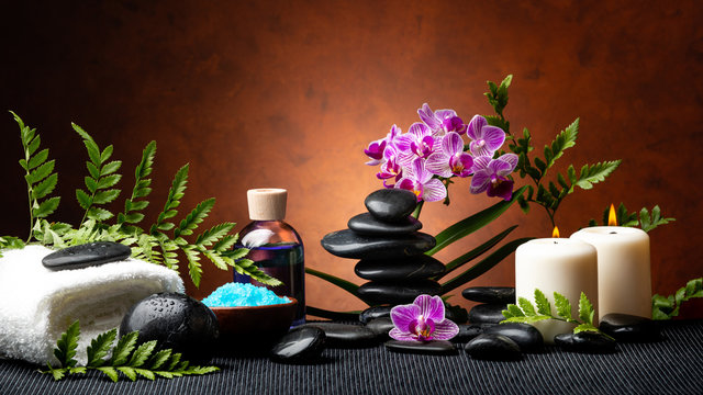 candle light spa treatment set with aromatic salt, perfumed essence, stones and orchid flowers with ornamental fern