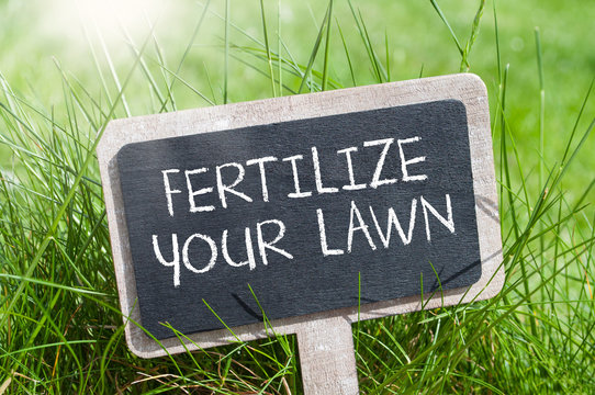 Chalkboard in the grass with fertilize your lawn