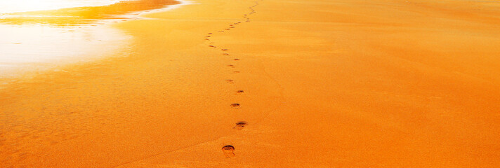 A series of footprints walking on the beach by the sea under the setting sun