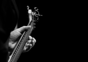 Wall Mural - The hand of a musician playing a guitar on a black background in black and white