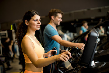Keuken foto achterwand Fitness Young woman and man on elliptical stepper trainer exercising in gym
