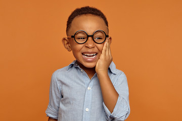 Emotional black dark-skinned little boy grimacing and holding hand on his cheek because of intolerable toothache. Handsome cheerful dark skinned African child in glasses and shirt smiling broadly Wall mural