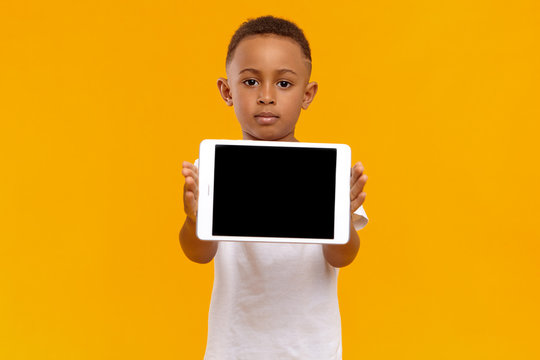 People, childhood and modern technology concept. Studio portrait of serious confident dark skinned kid holding digital tablet, showing blank display with copyspace for your text or advertising content