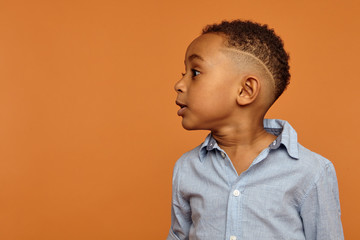 Waist up up image of handsome adorable dark skinned little child with stylish hairdo having emotional facial expression, standing isolated at blank orange wall with copyspace for your advertisement