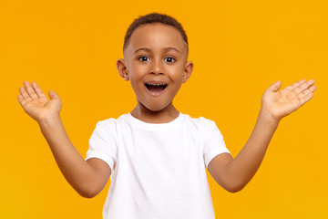 I'm so happy. Picture of overjoyed excited black little boy of African origin exclaiming emotionally and gesturing actively with both hands, amazed with good news, receiving highest mark for test Wall mural