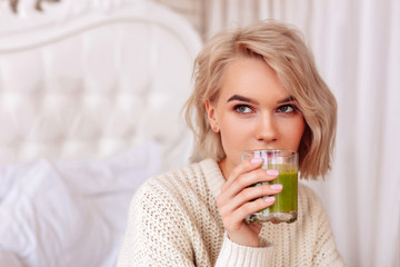 Blonde-haired woman drinking healthy green juice in bedroom