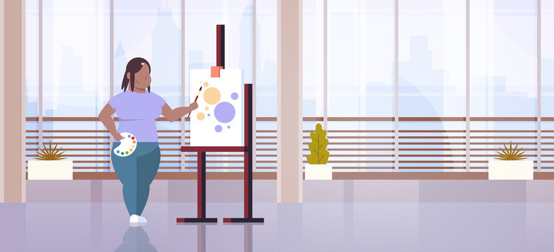 fatty obese woman painter holding paintbrush african american overweight girl artist painting process art workshop studio interior full length flat horizontal