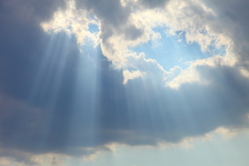 Ray of sun light shine through the gap among cloud with blue sky