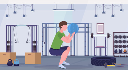 sporty man doing squats exercises with medicine leather ball guy training cardio workout concept modern gym health studio club interior horizontal full length