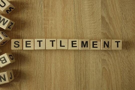 Settlement word from wooden blocks on desk